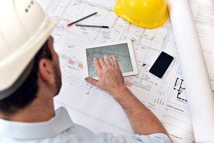Planung und Entwicklung im Bauwesen - Architekt mit Tablet und techn. Zeichnung am Arbeitsplatz